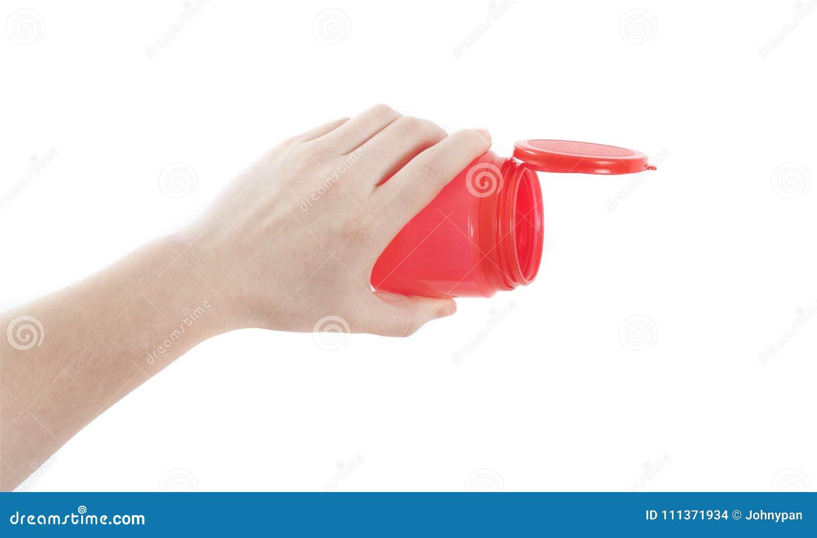 Рука держа пустой красный цвет может или бутылка для лить концепции