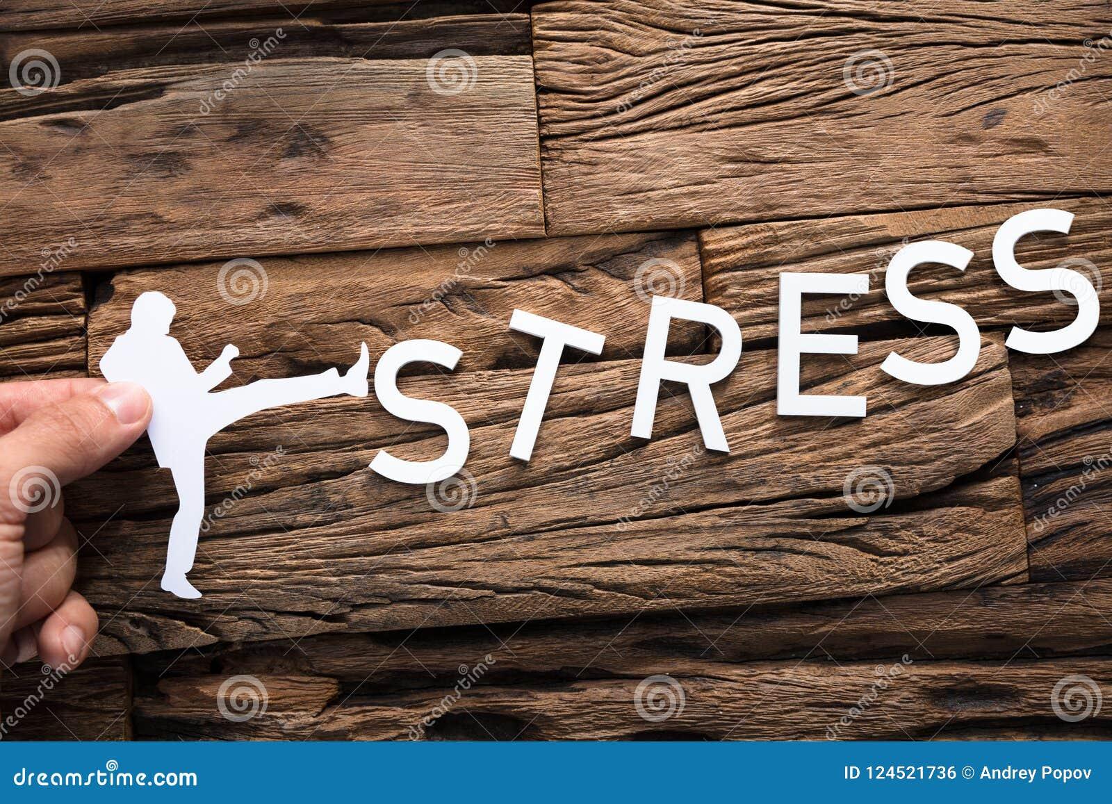 Рука держа стресс слова бумажного бизнесмена пиная