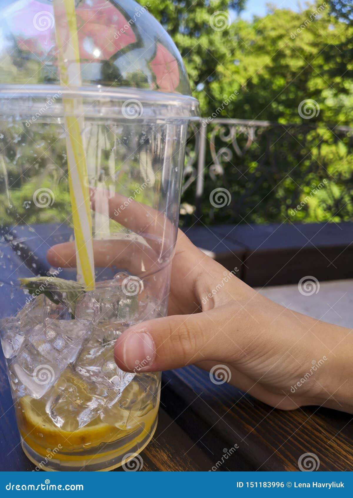Рука держа чашку лимонада пластиковую с соломой