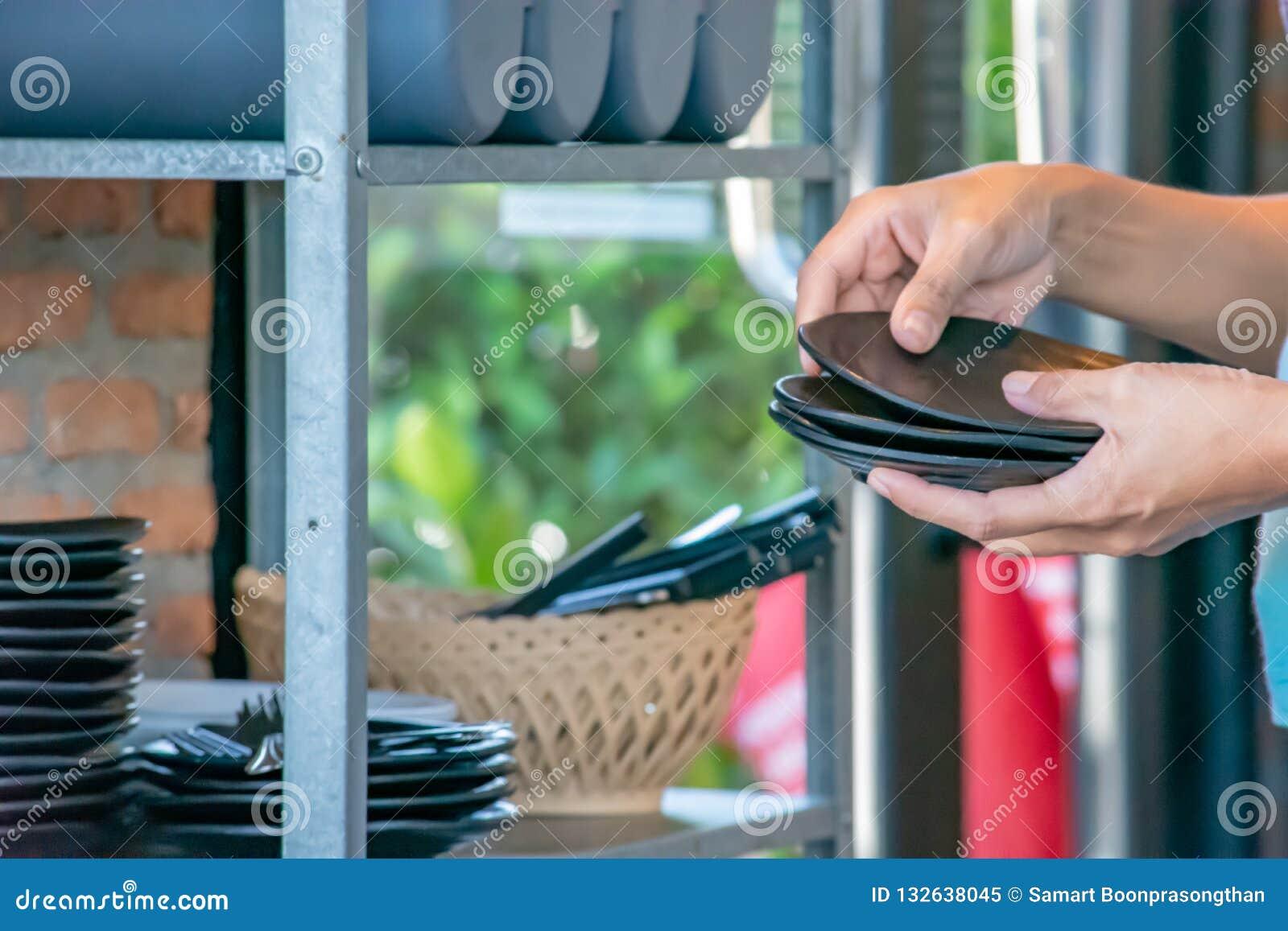 Рука держа черную плиту и шкаф блюда