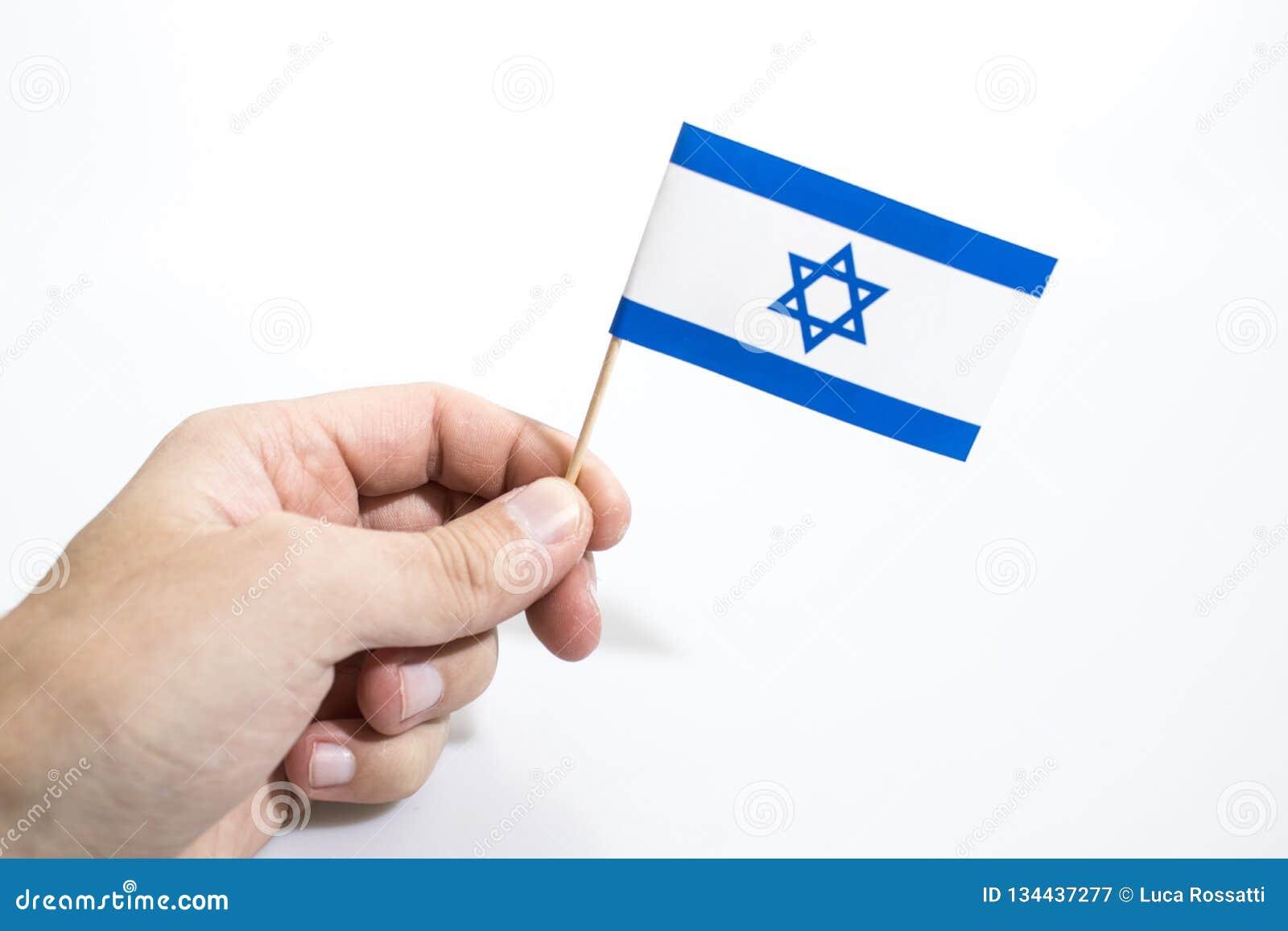 Рука держит флаг Израиля изолированный в белой предпосылке