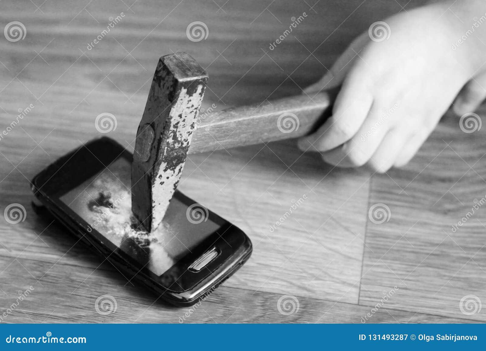 Рука детей с молотком ломает смартфон, черно-белый