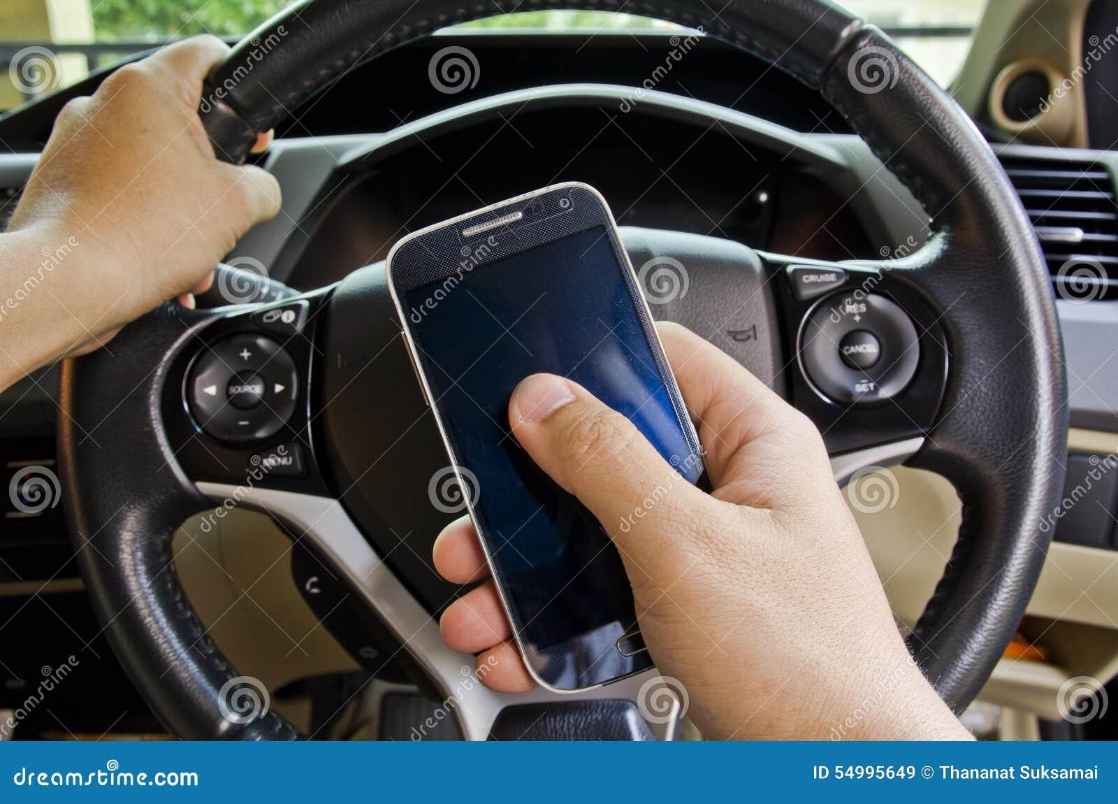 Рука держа мобильный телефон в автомобиле