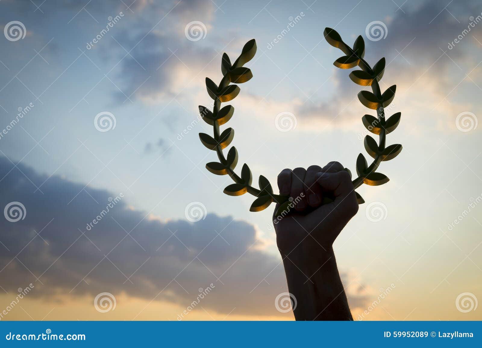 Рука держа небо захода солнца лаврового венка