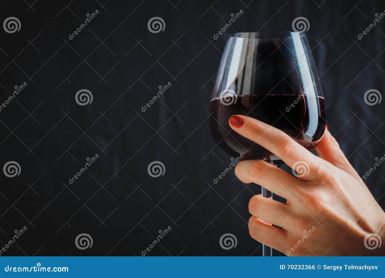 Рука держа стекло красного вина