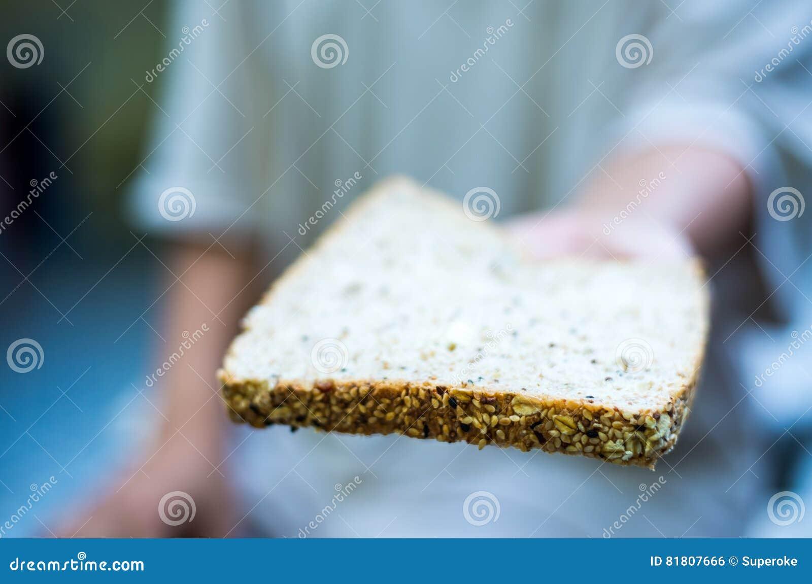 Рука держа хлеб всей пшеницы