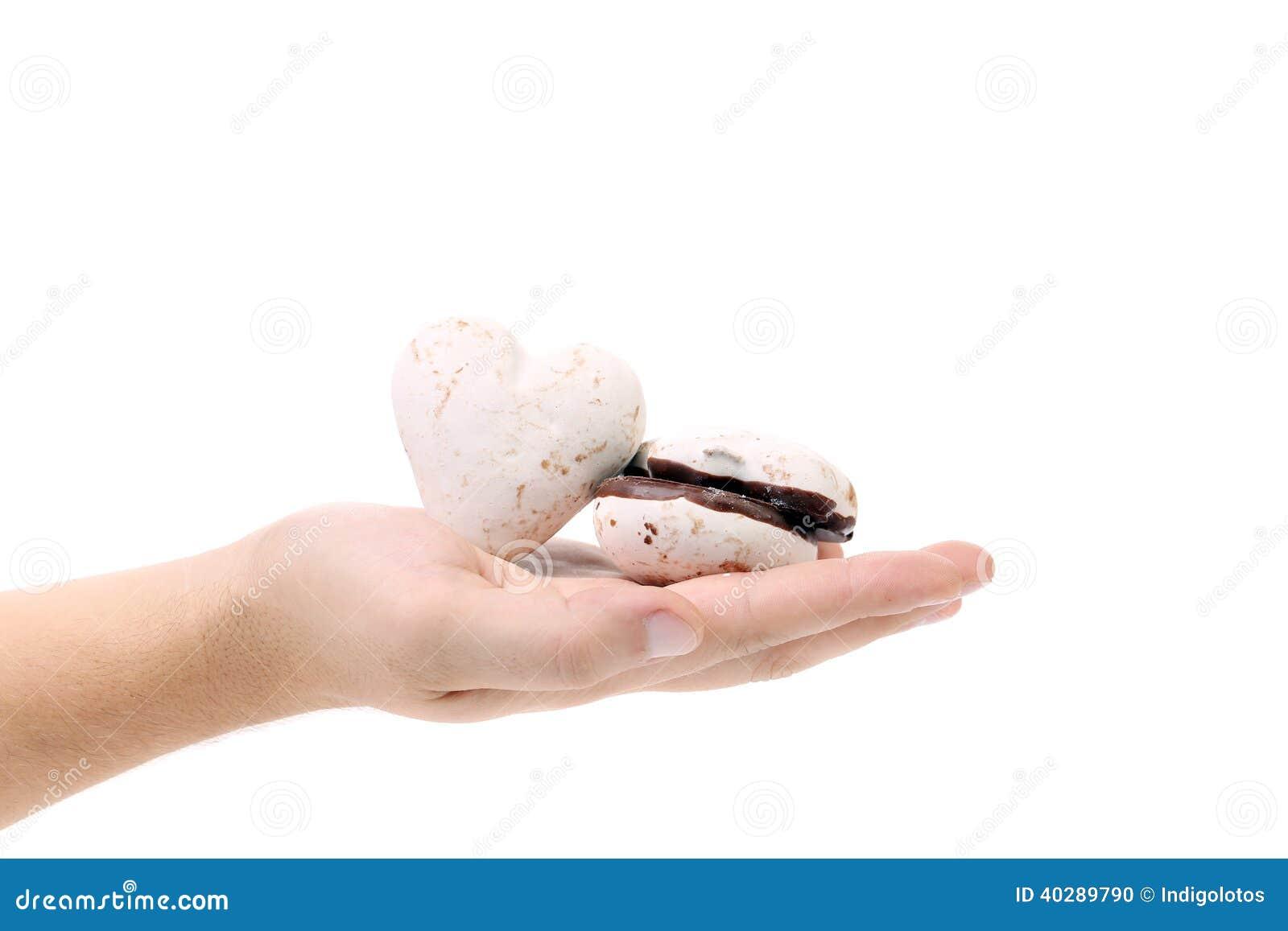 Рука держит печенья сформированные сердцем.