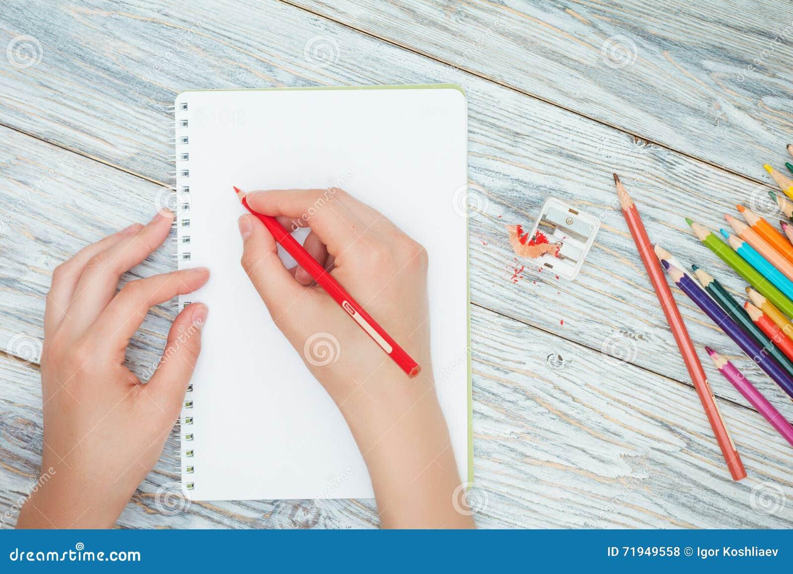 Рука держит покрашенный карандаш