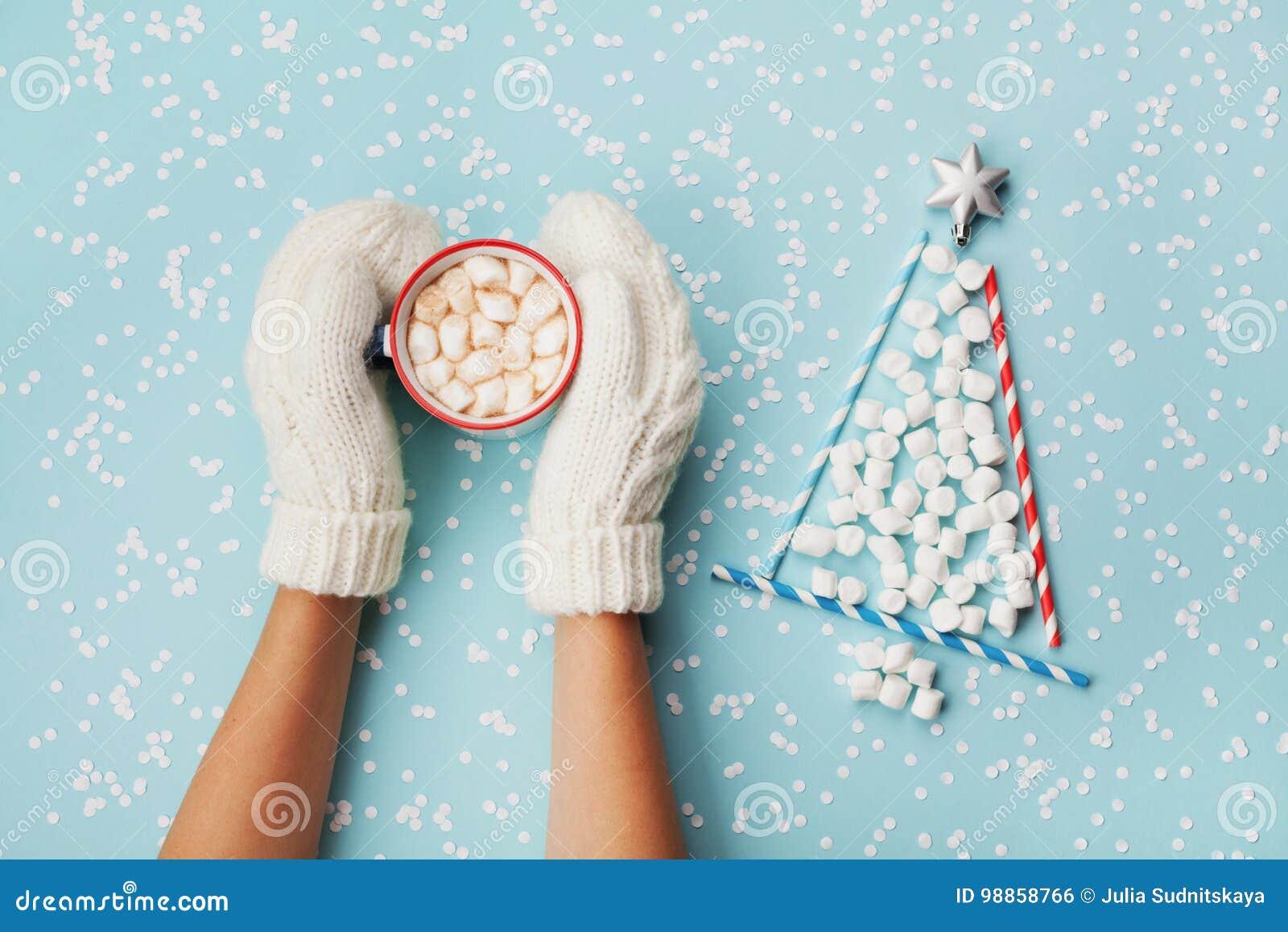 Рука женщины в чашке владением mitten горячих какао или шоколада и ели рождества сделанной из зефира украсила серебряную звезду