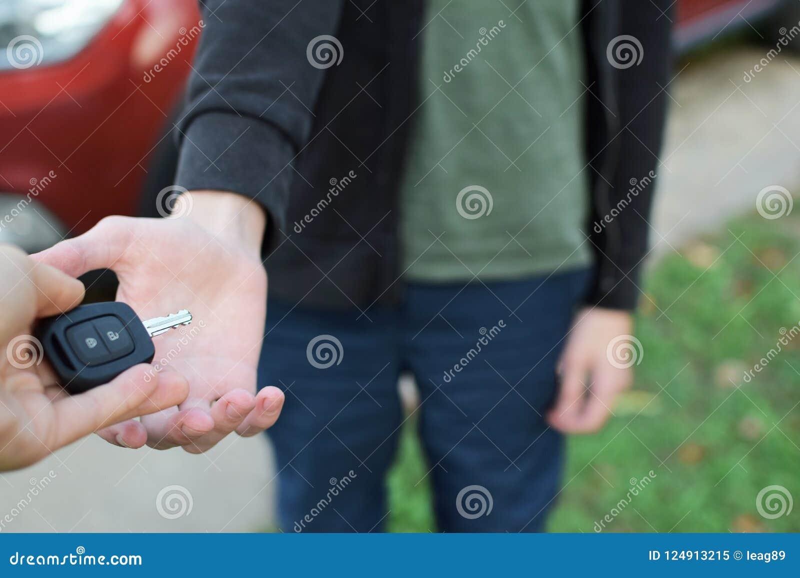 Рука женщины давая ключ автомобиля