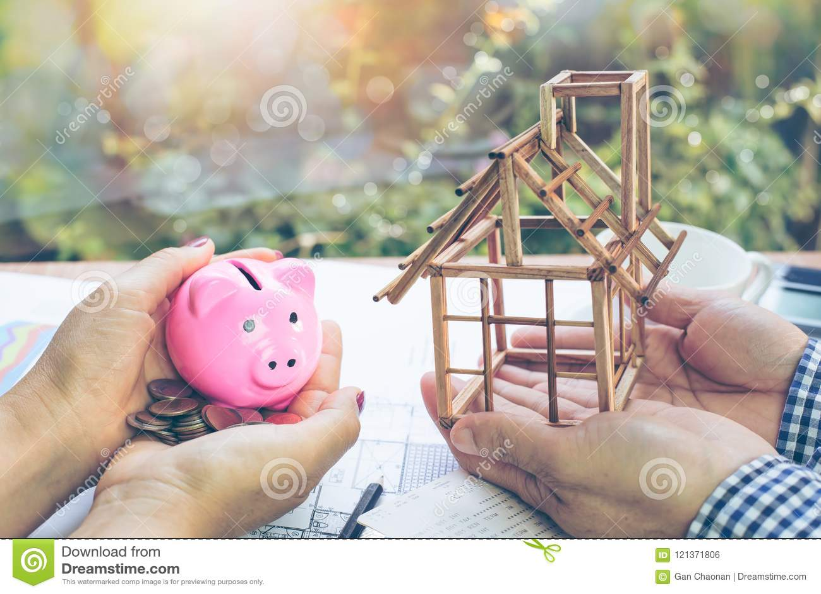 Рука женщины держа копилку и монетку в ее руке и руках людей которые держат модельный дом под const