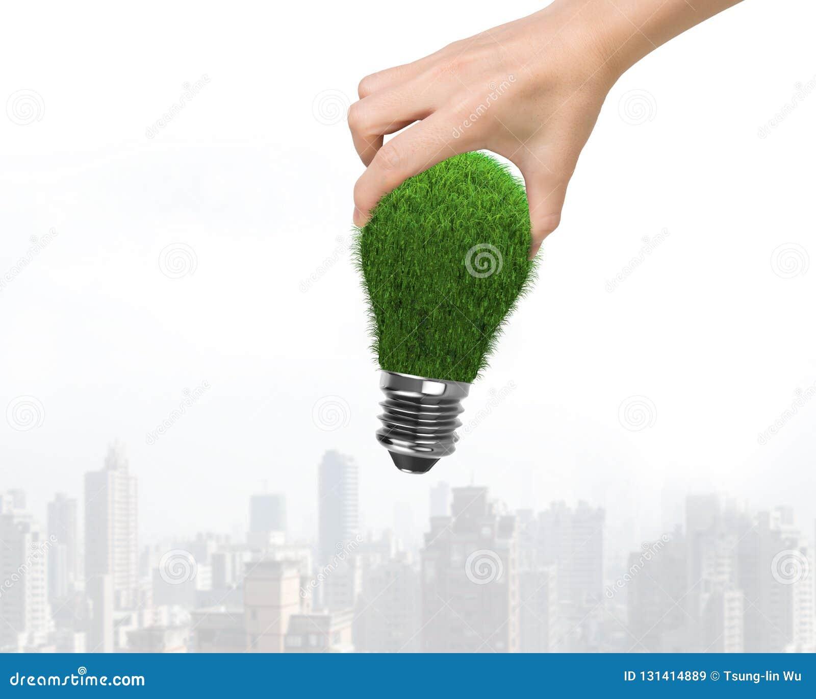 Рука женщины держа одну электрическую лампочку с зеленой травой, на небоскребах предпосылке, концепции ECO и зеленой энергии здан