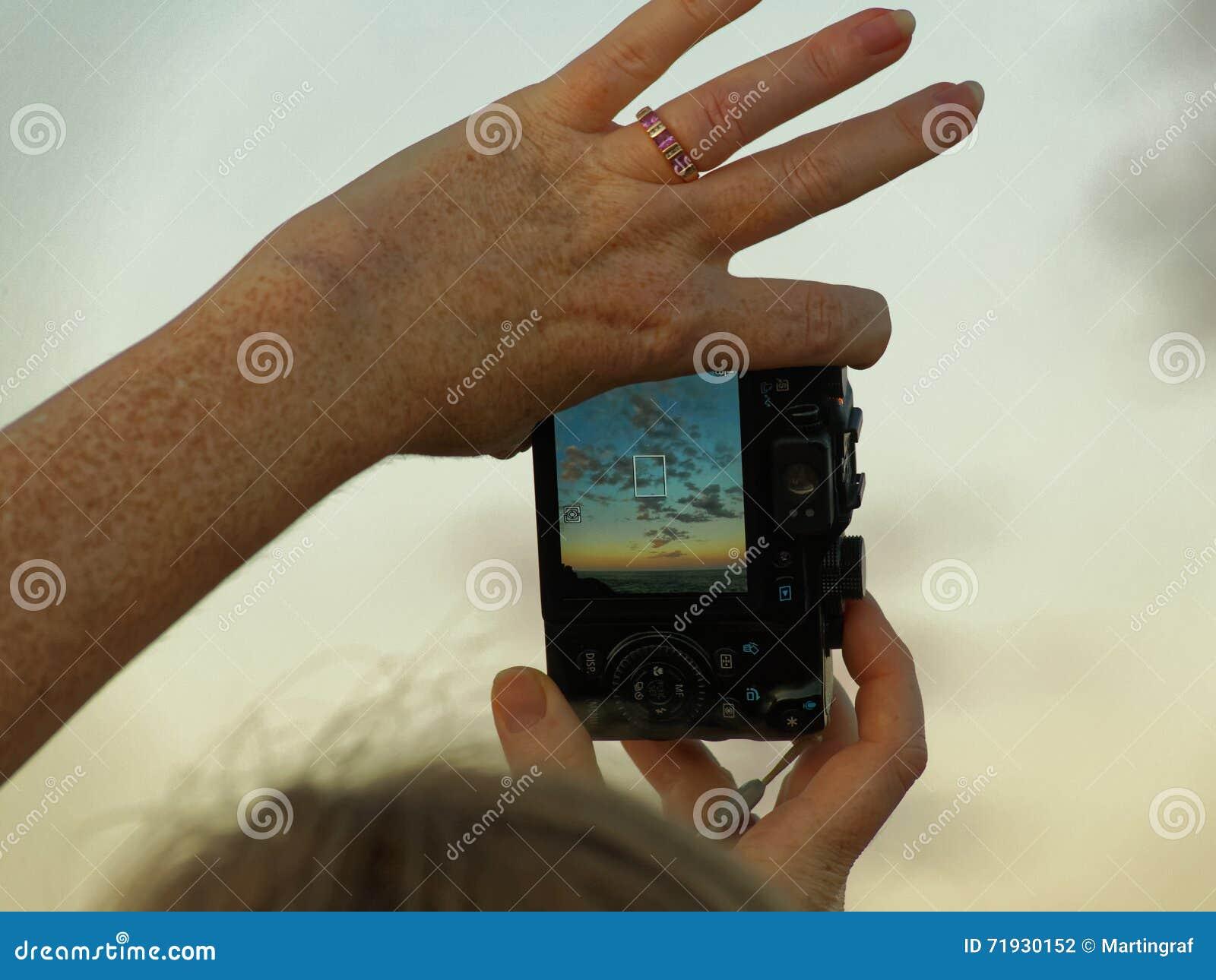 Рука женщины держит камеру с небом захода солнца на экране