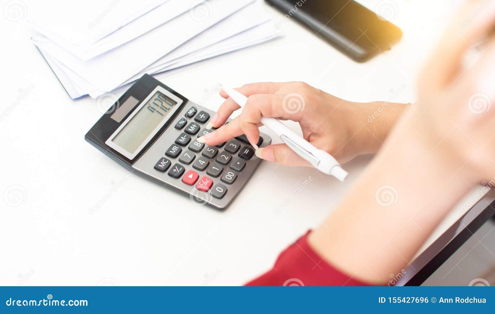 Рука женщины использует калькулятор