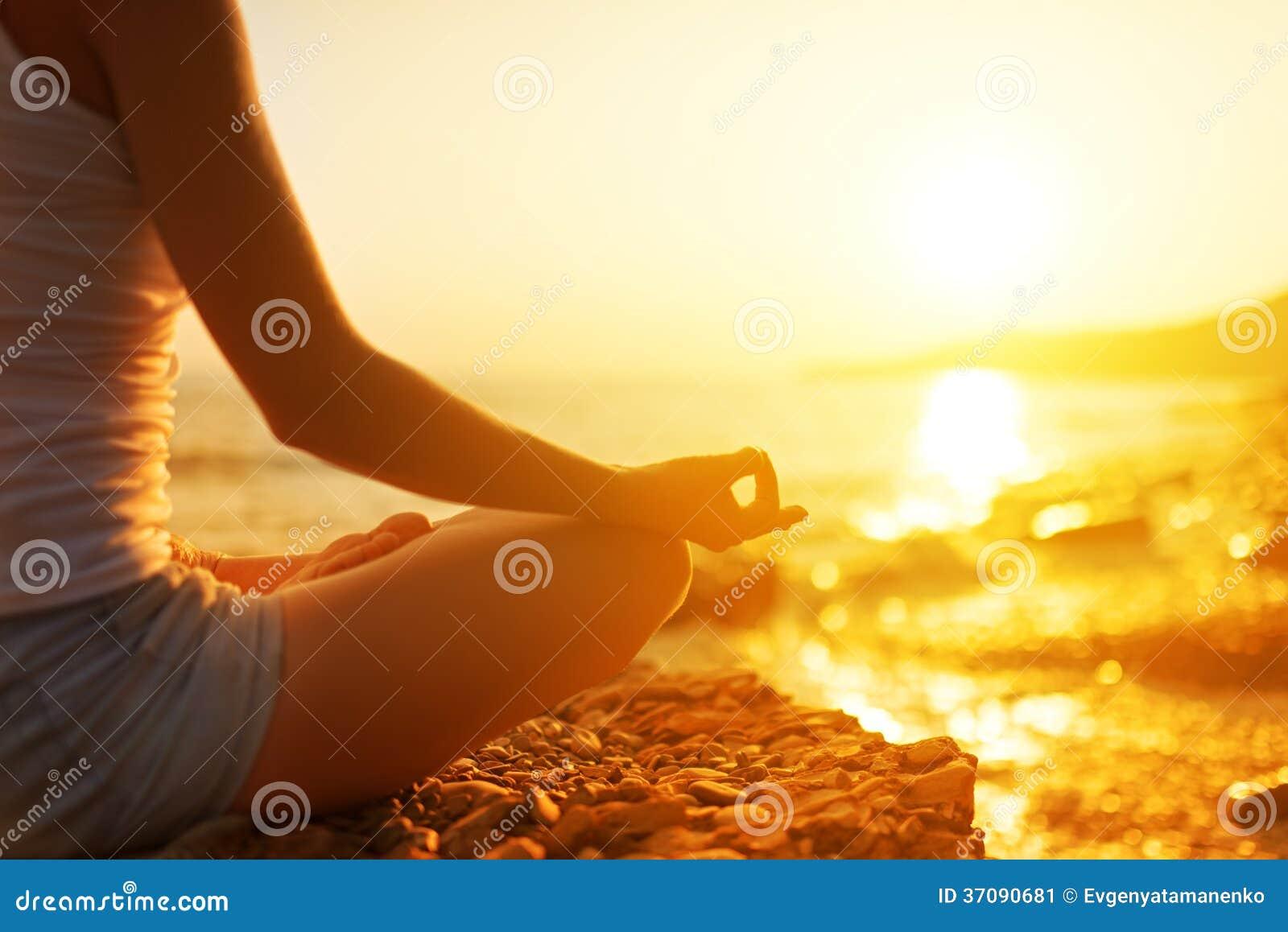 Рука женщины размышляя в представлении йоги на пляж