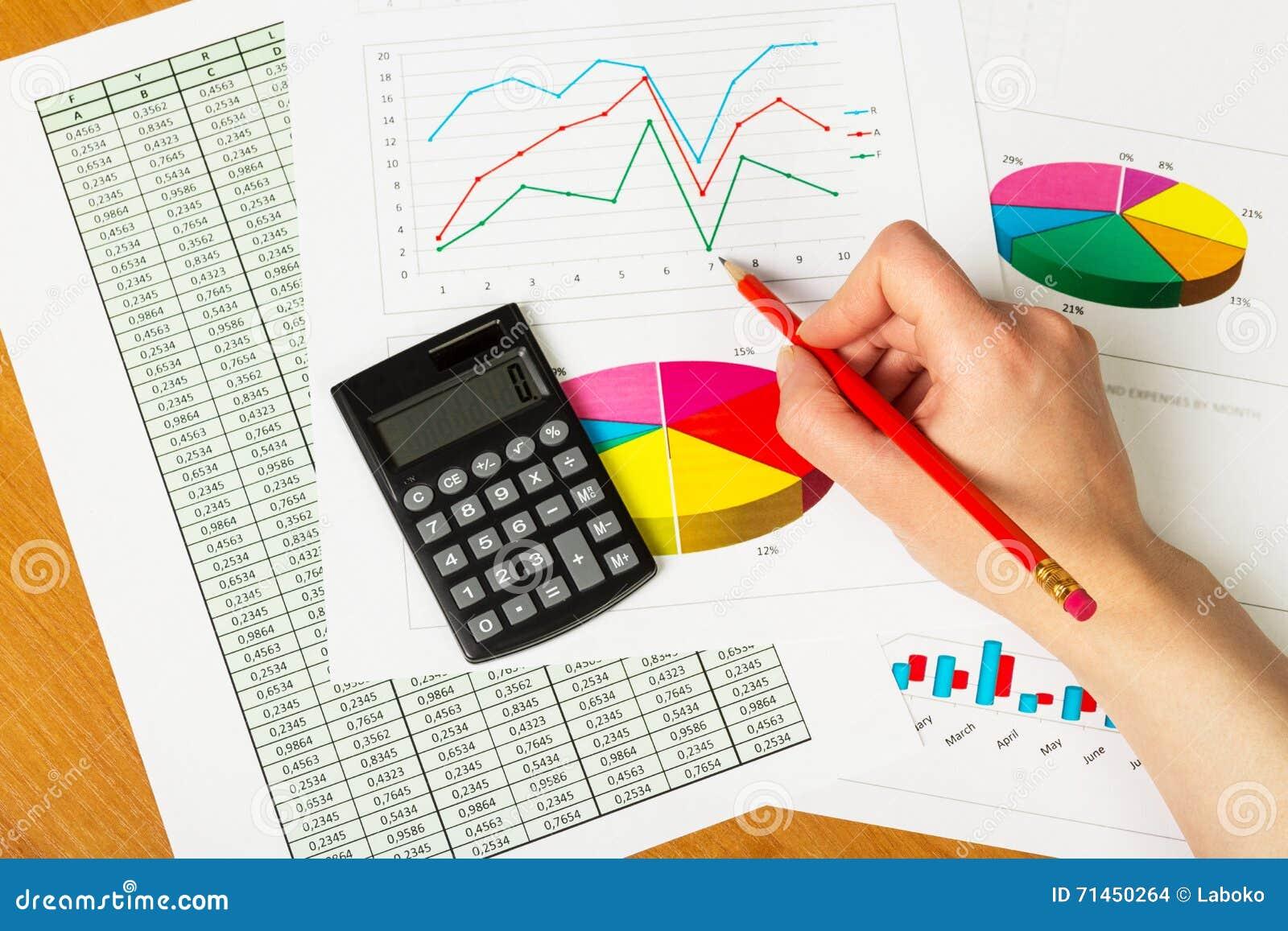 Рука женщины рисует диаграмму на предпосылке стола офиса