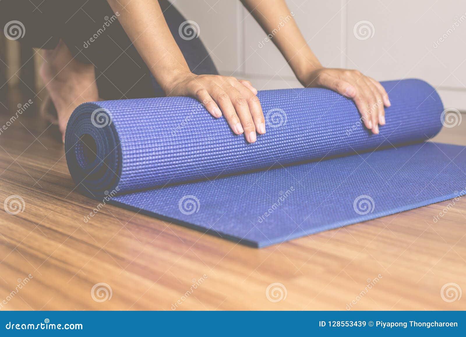 Рука женщины свертывая или складывая голубую циновку йоги после фитнеса разминки, оборудования тренировки здоровых и концепции сп