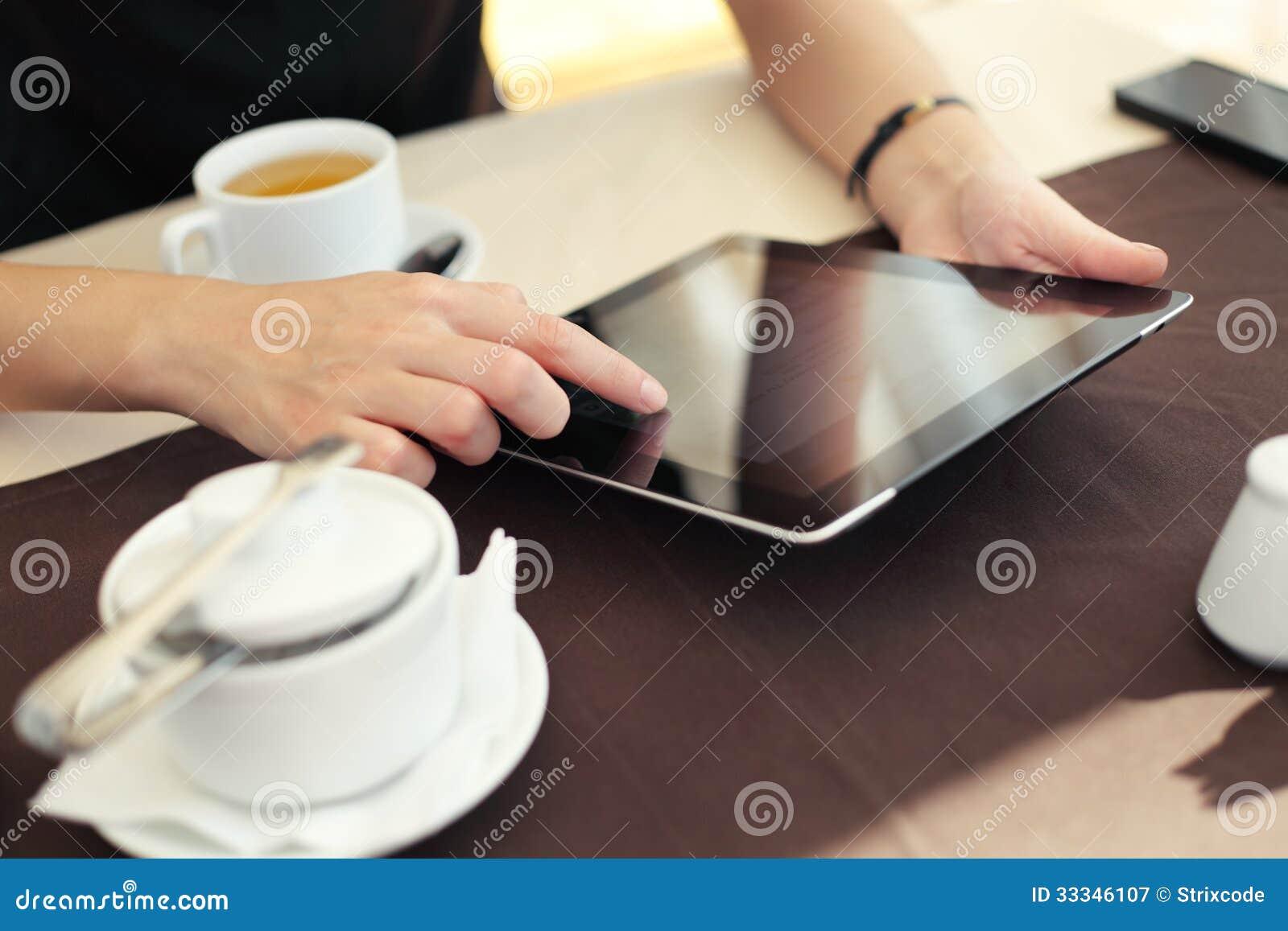 Рука женщины указывая на сенсорный экран таблетки в кафе