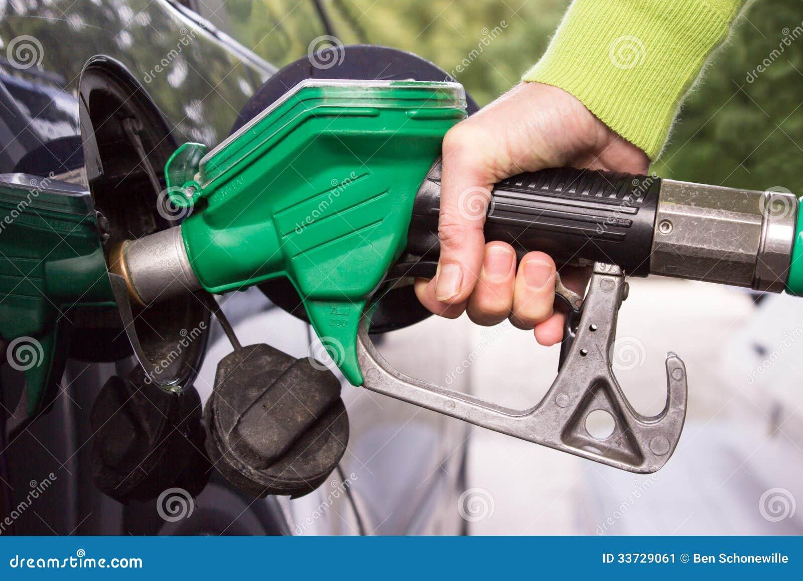 Рука заполняя танк автомобиля с бензином