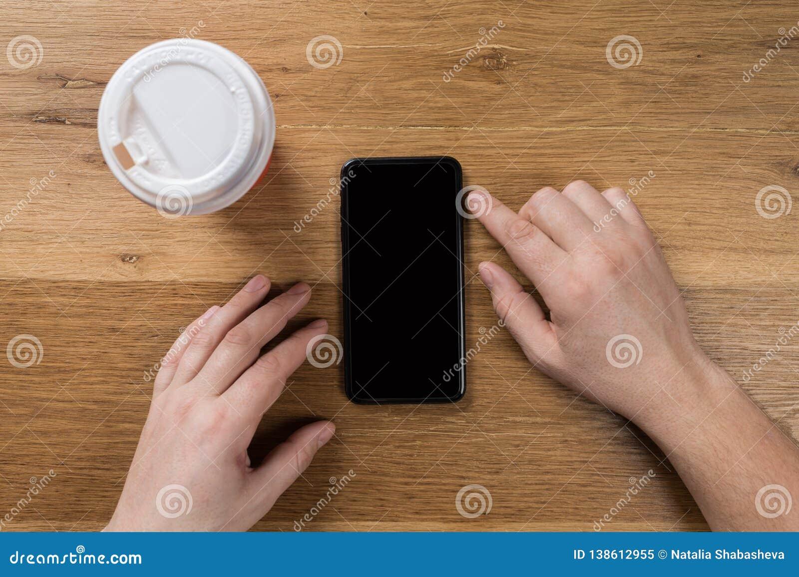 Рука используя взгляд сверху телефона