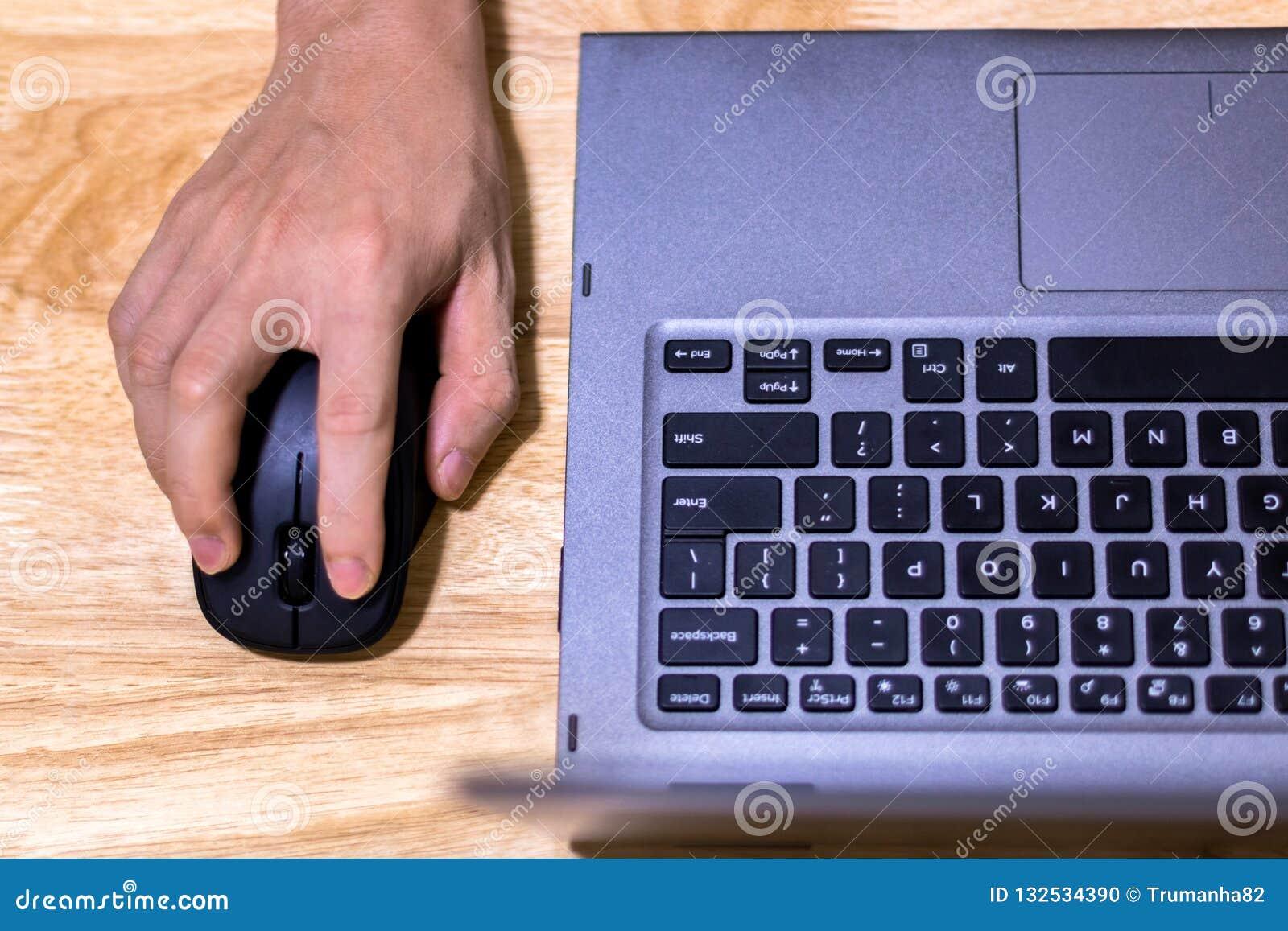 Рука используя мышь и ноутбук компьютера на столе