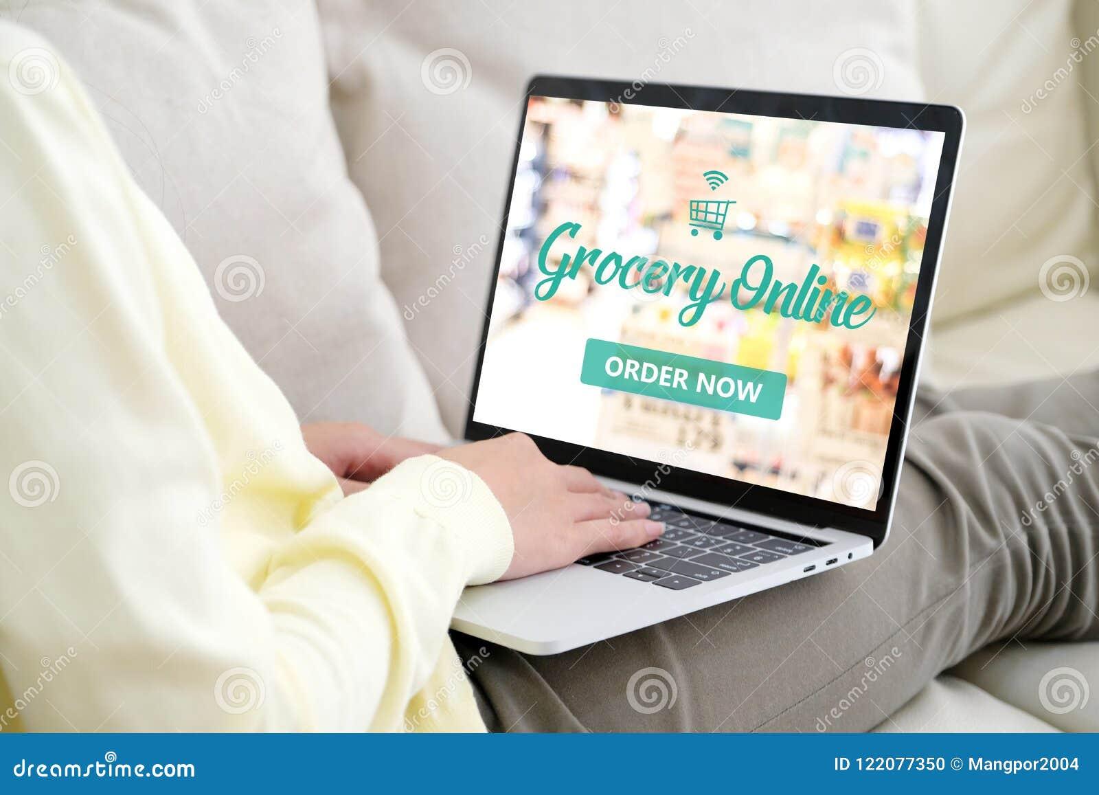 Рука используя портативный компьютер с покупками бакалеи онлайн над голубым