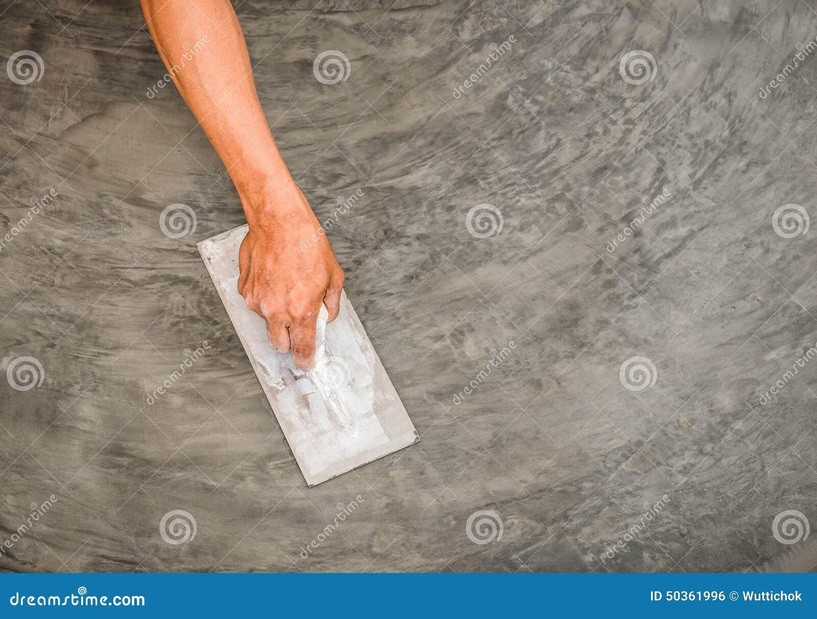 Рука используя стальную лопатку для того чтобы закончить отполированную влажную конкретную поверхность