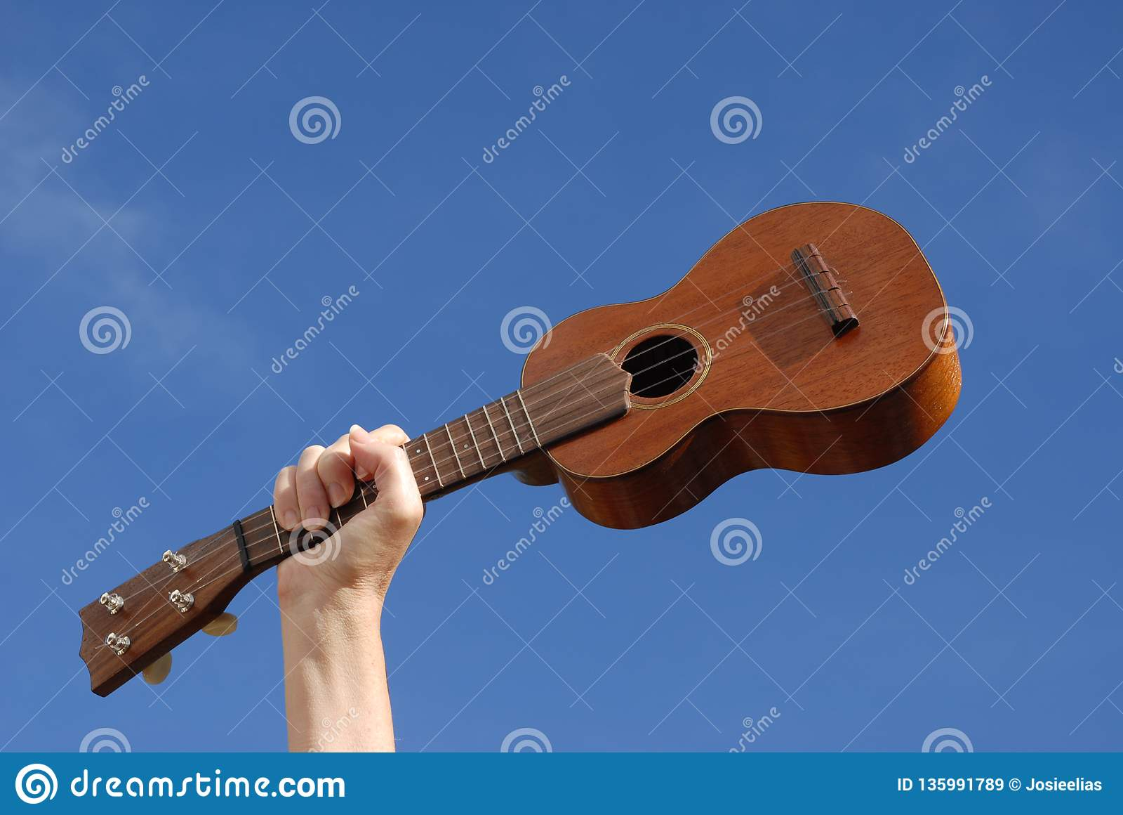 Рука и гавайская гитара против голубого неба