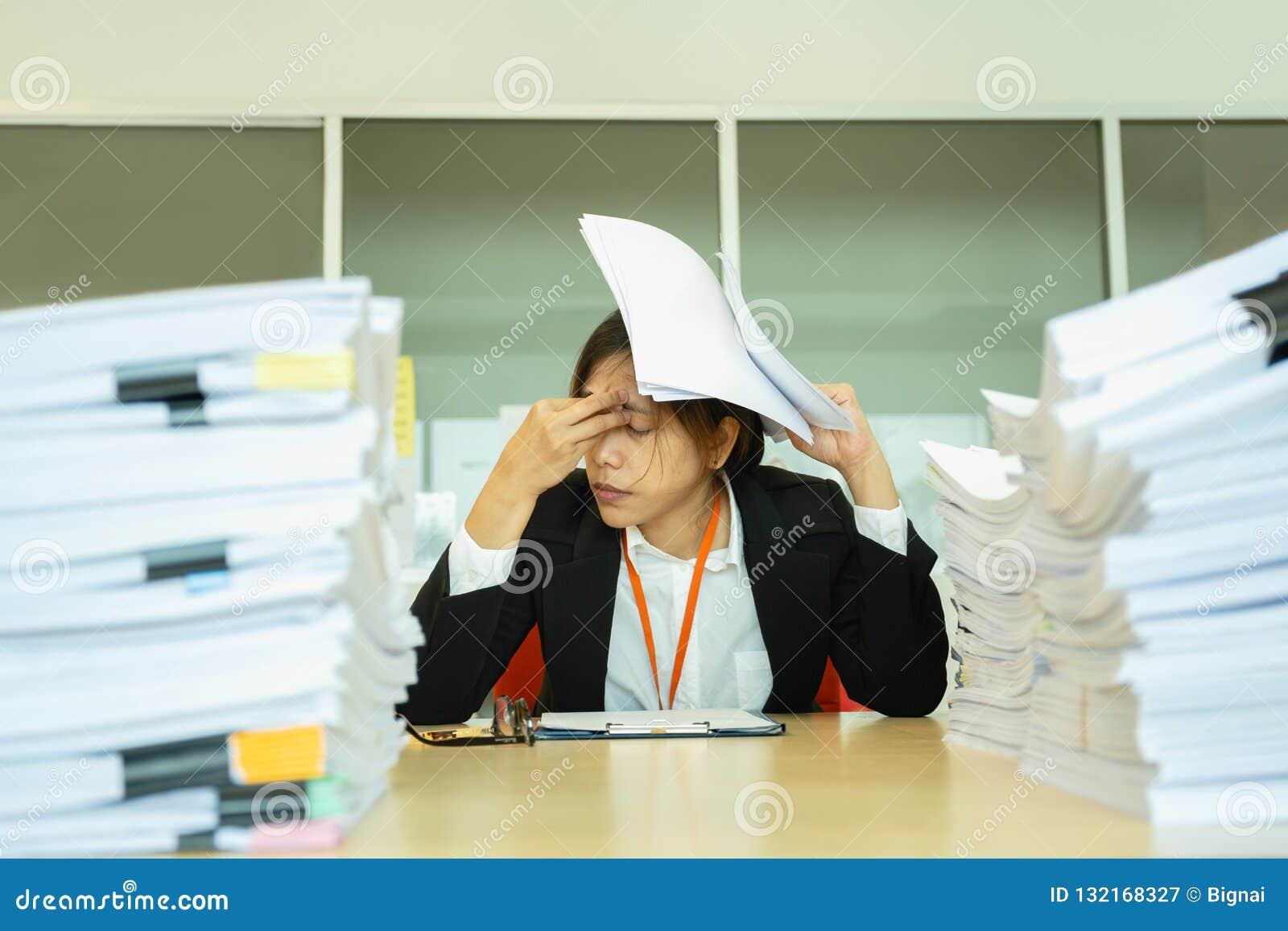 Рука коммерсантки отдыхая на главных глазах близких с кучей обработки документов