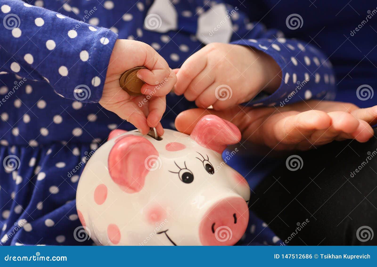 Рука маленькой девочки ребенка кладя монетки в piggybank