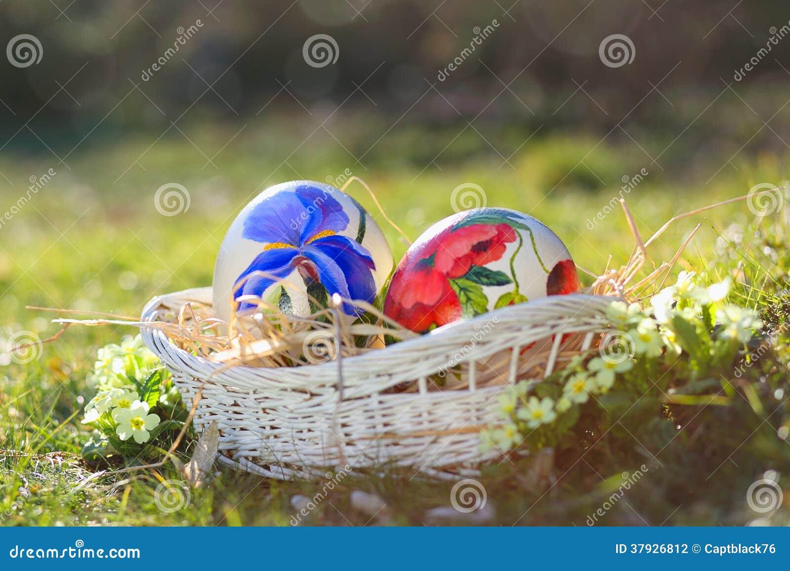 Рука пасхальных яя покрашенная в плетеной корзине