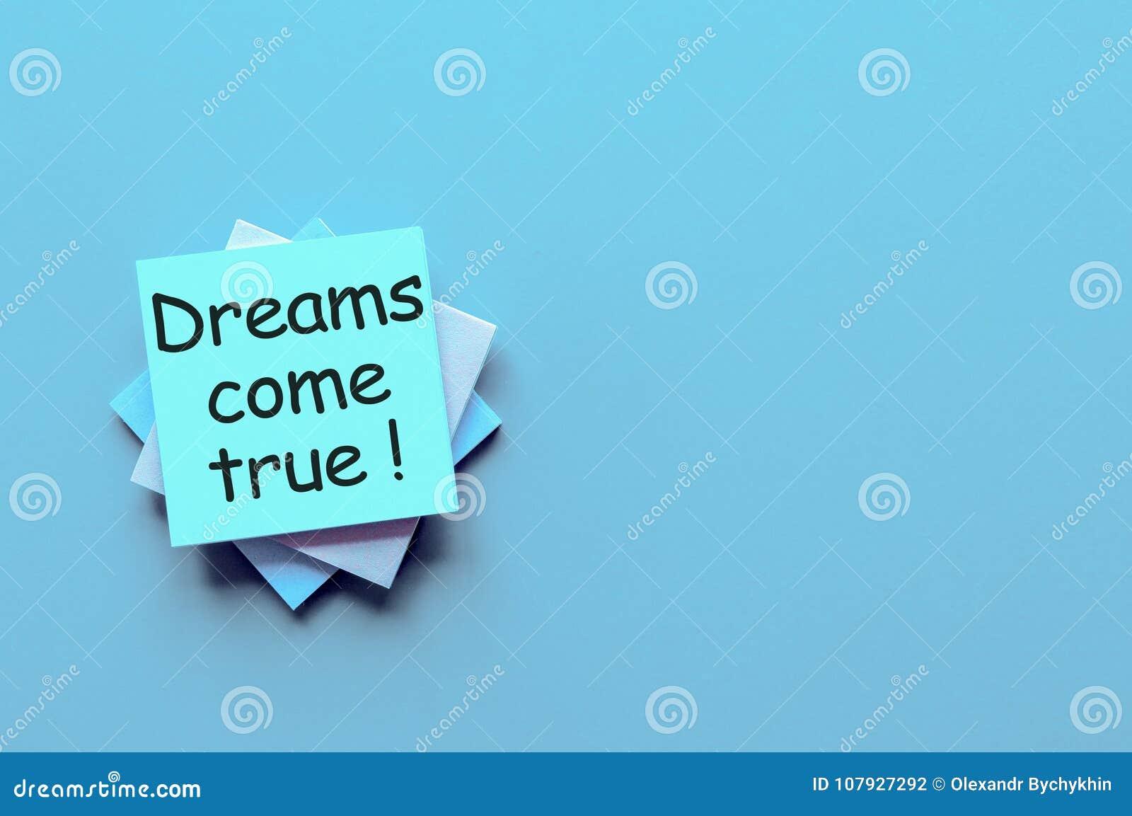 Рука пишет мечты приходит верно - на свете - голубая предпосылка с пустым космосом для текста и глумится вверх