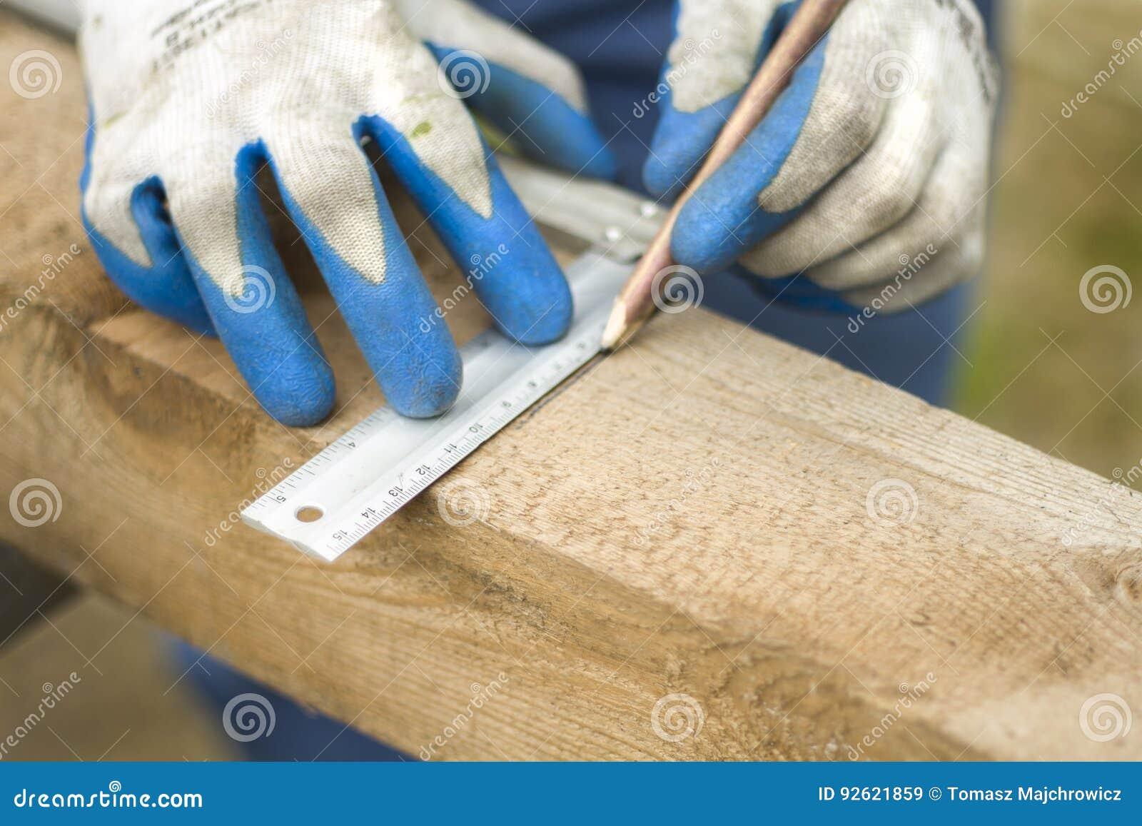 Рука рабочий-строителя указывает с карандашем расстояние на деревянном крае