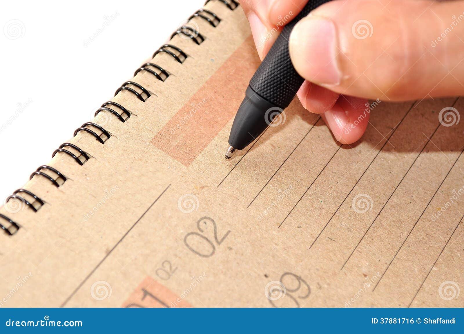 Рука с ручкой принимает примечание в календарь