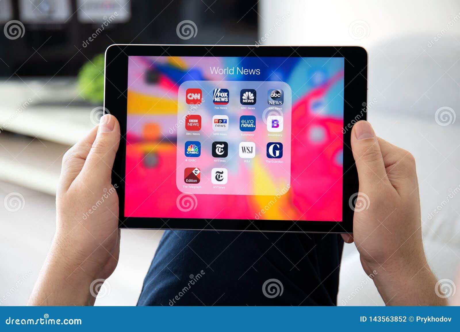 Рука человека держа iPad Pro с популярными применениями новостей