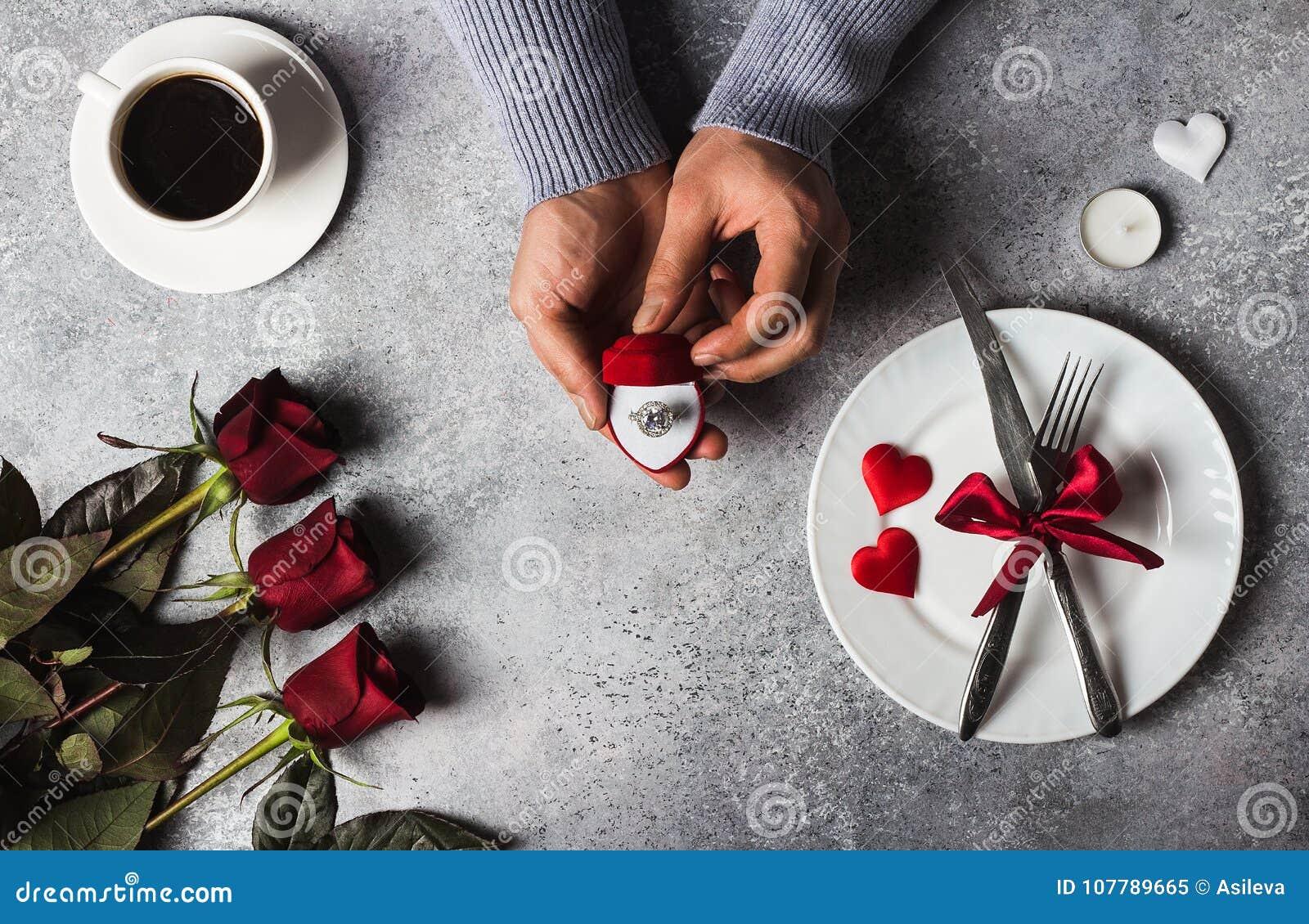 Рука человека сервировки стола обедающего дня валентинок романтичная держа обручальное кольцо