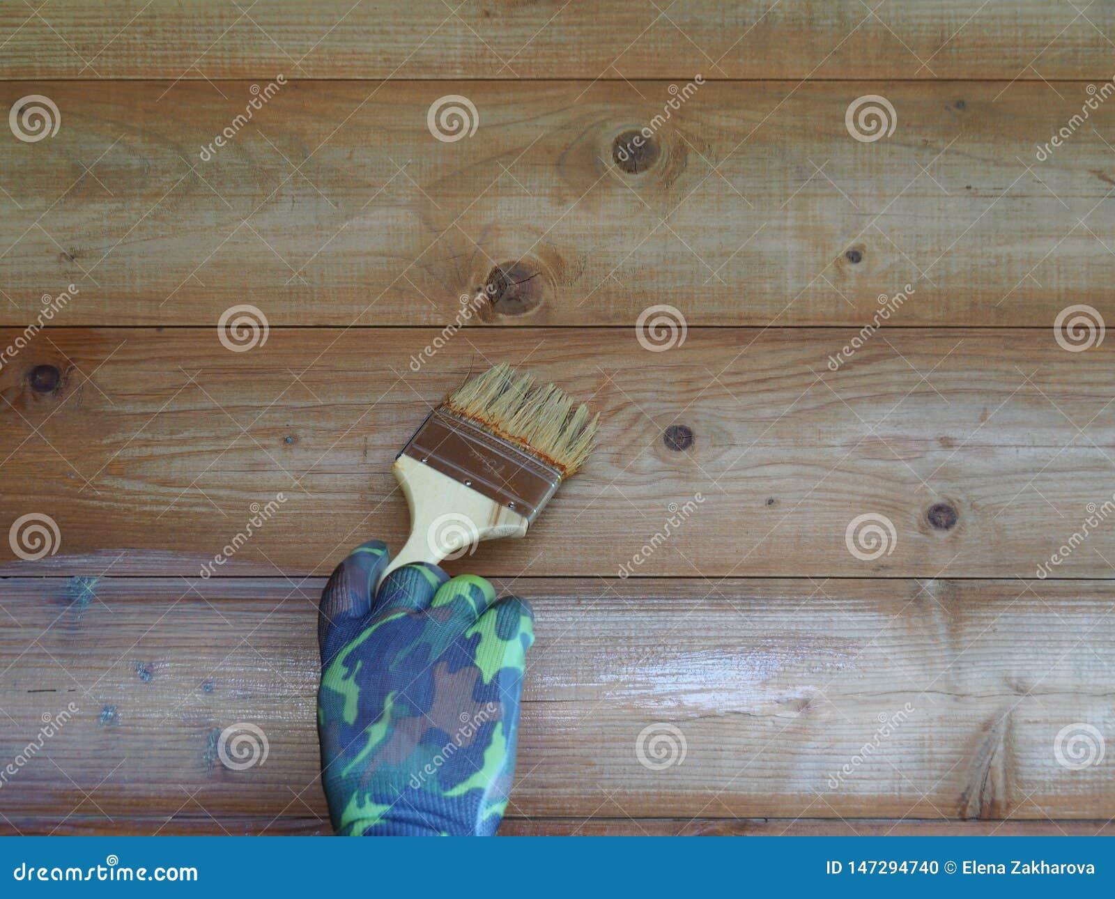 Рука человека с щеткой для того чтобы покрасить деревянную стену