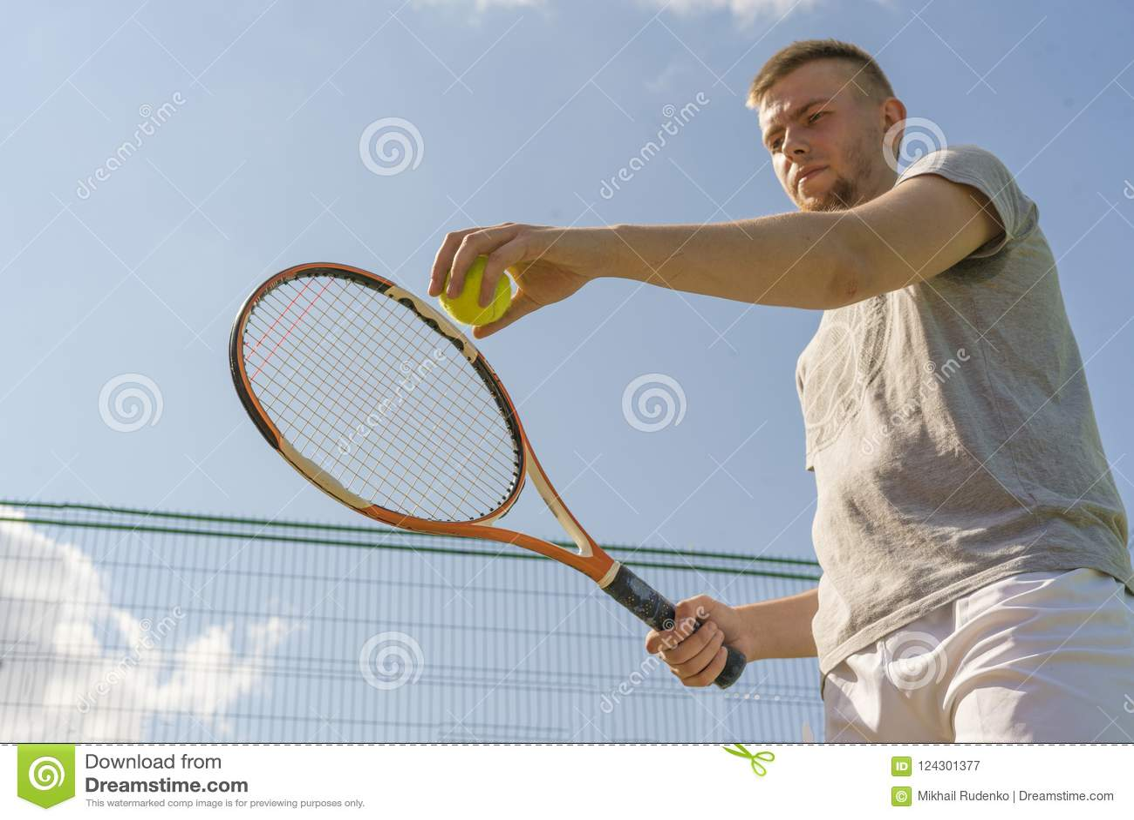 Рука человека теннисиста делая съемку держа шарик и ракетку против неба