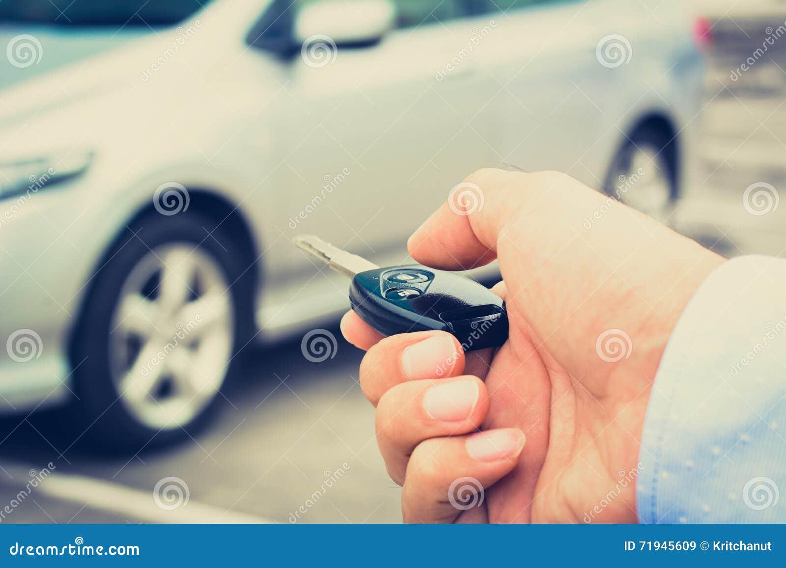 Рука человека около для того чтобы отжать кнопку ключа автомобиля дистанционного управления
