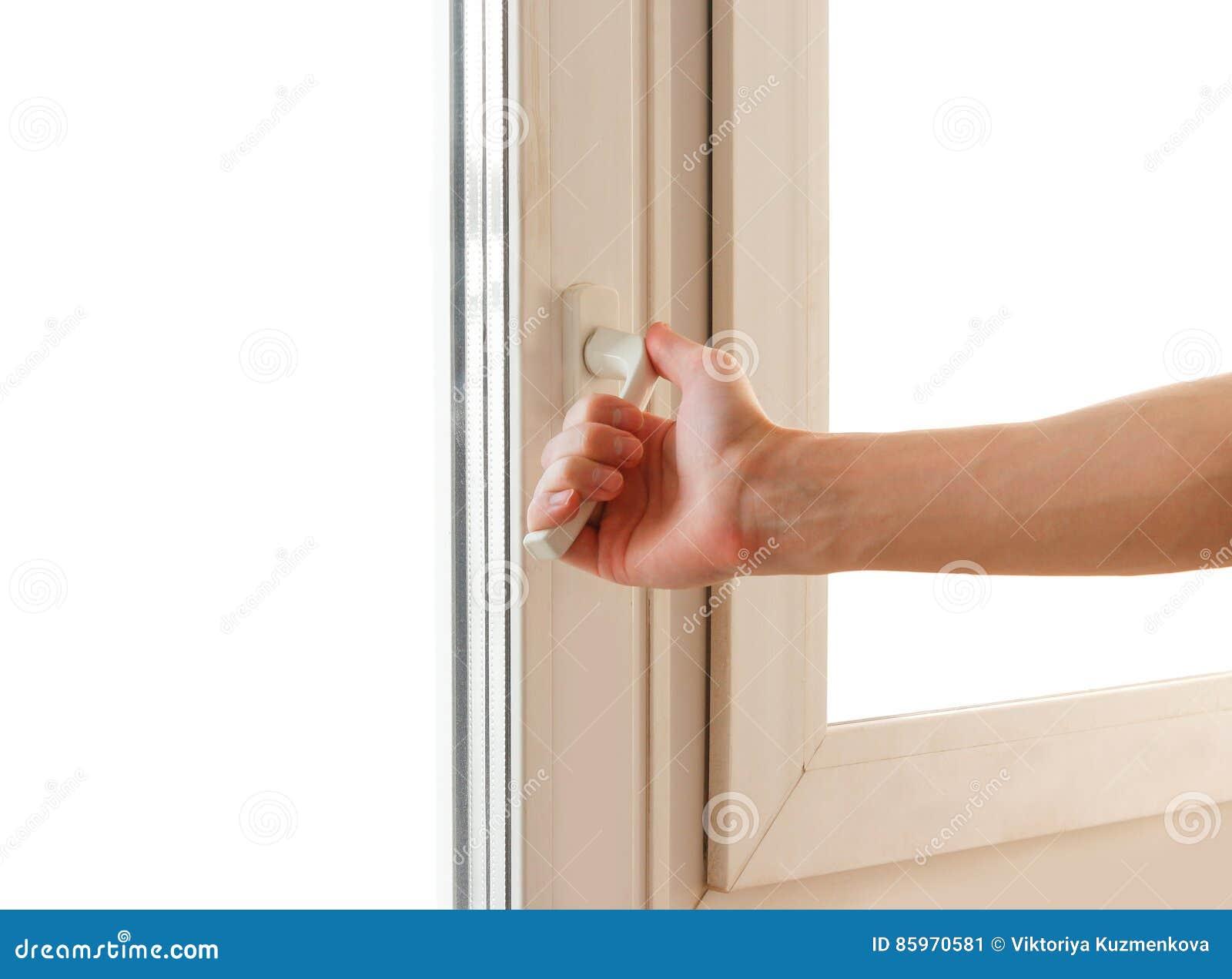 Рука человека раскрывает белую пластмассу окно Изолировано на белизне