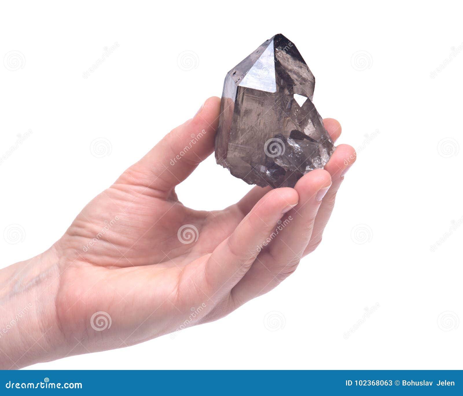 Рука ` s женщины держа кварц Gwindel кварца Smokey большой возвышенности