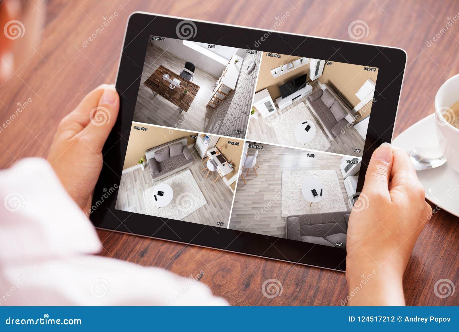 Рука ` s персоны смотря дома камеры слежения