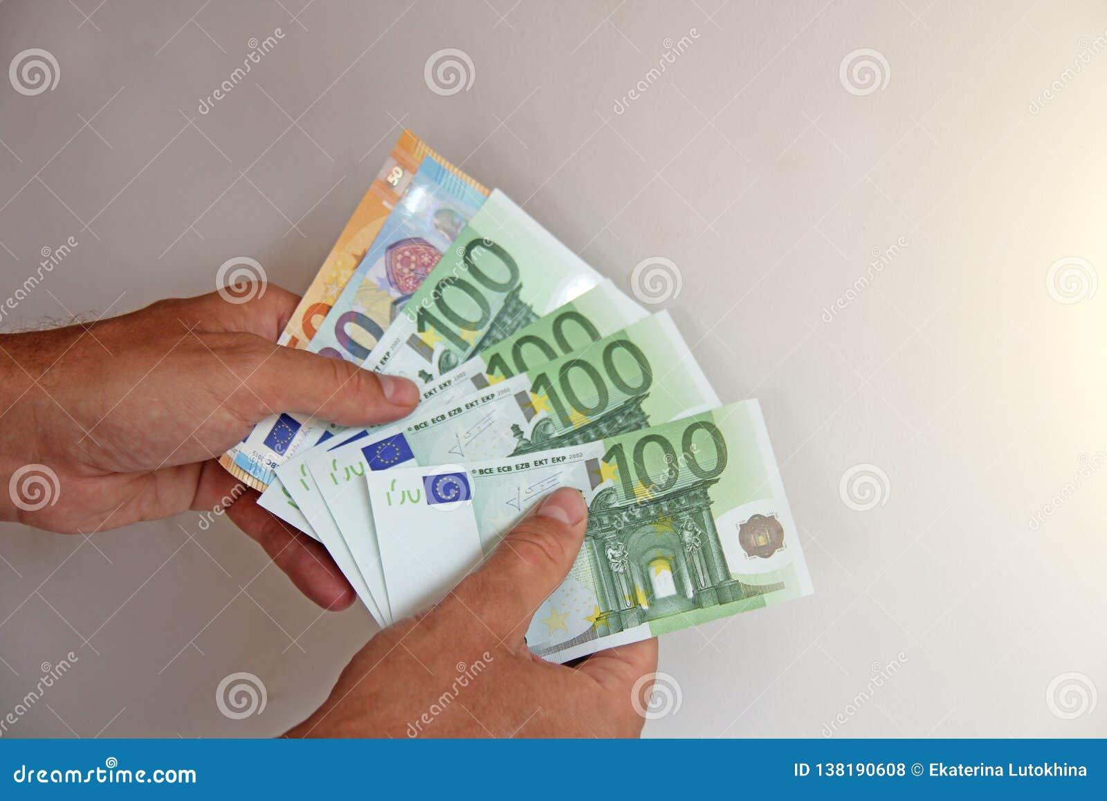 Рука ` s человека держит евро 100, рассматривает их и оплачивает Евро бумажных денег в руках
