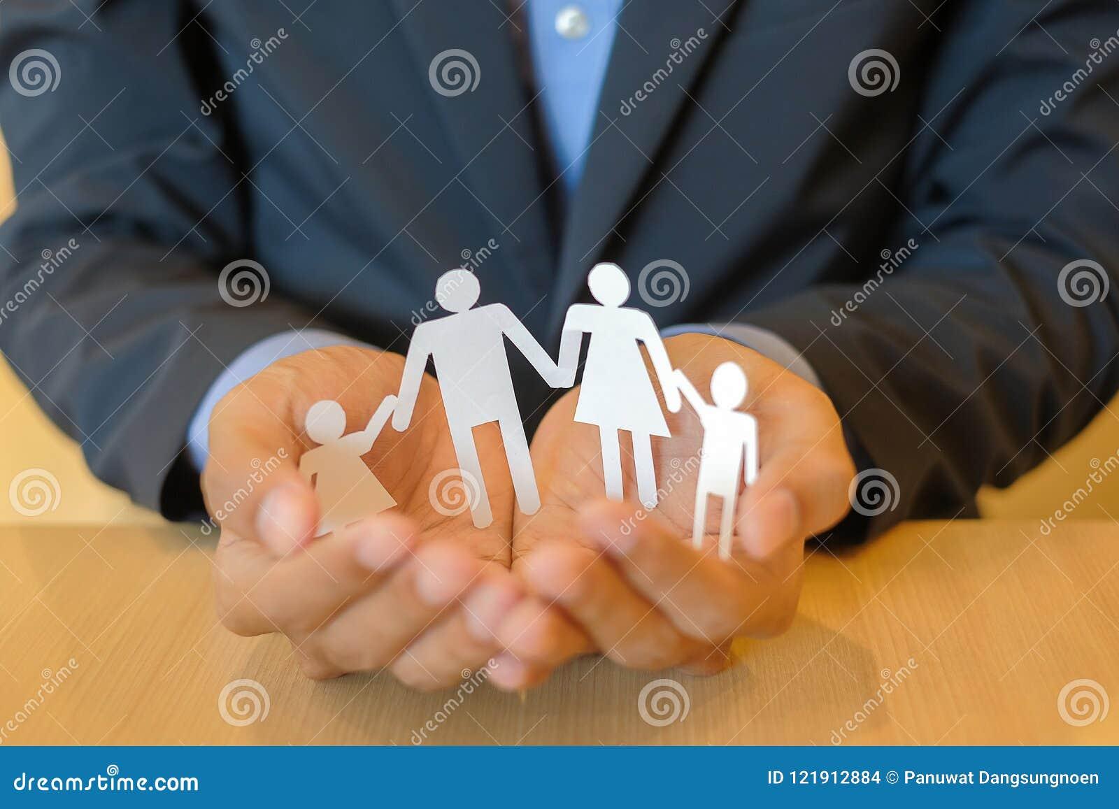 Руки бизнесмена держа бумагу семьи Концепция здравоохранения и страхования