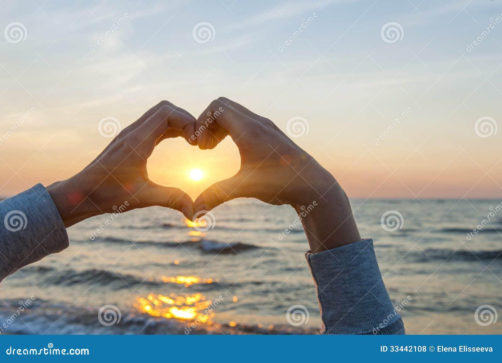 Руки в солнце формы сердца обрамляя