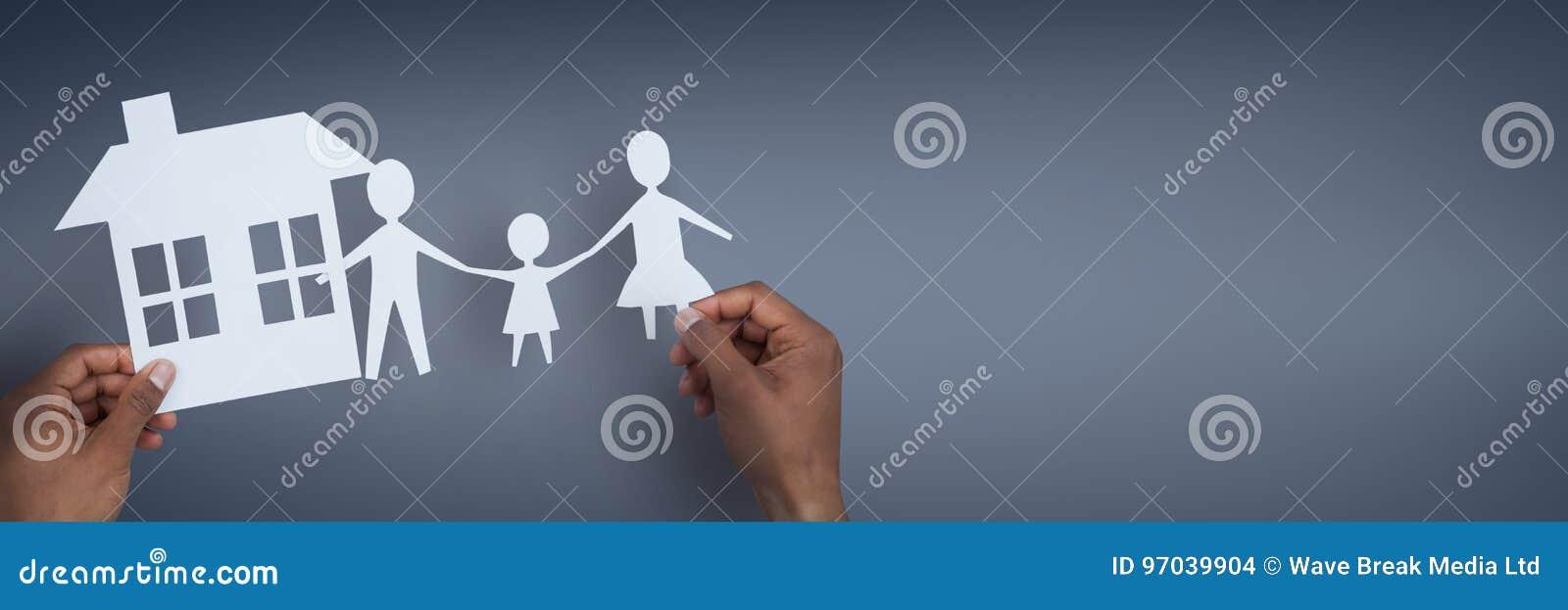 Руки держа бумажные диаграммы против голубой предпосылки как концепция страхования дома и семьи