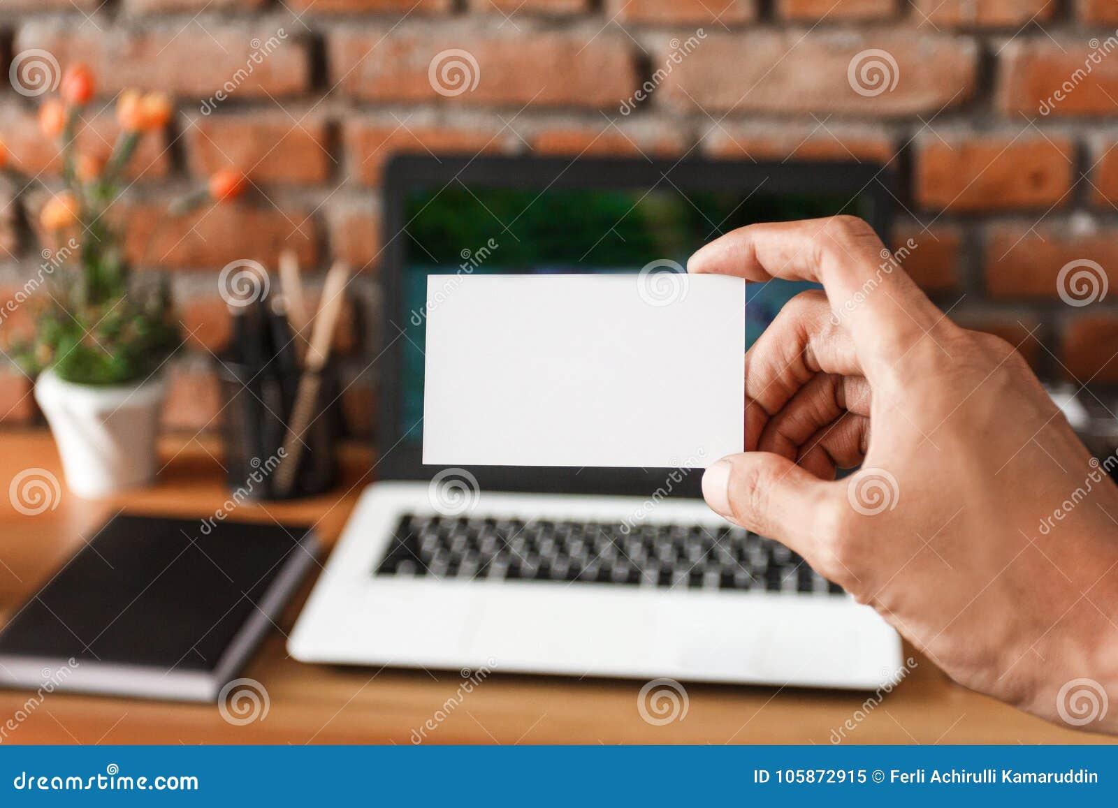 Руки держа визитную карточку с рабочей зоной на предпосылке