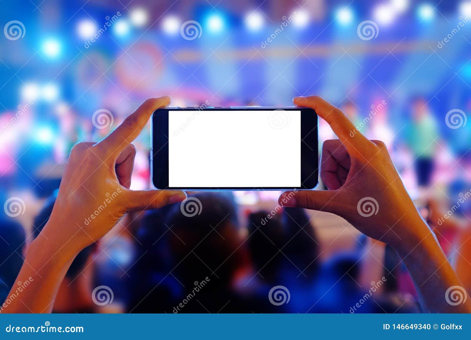 Руки держа мобильный смартфон записывают красочный концерт в реальном маштабе времени с пустым белым экраном