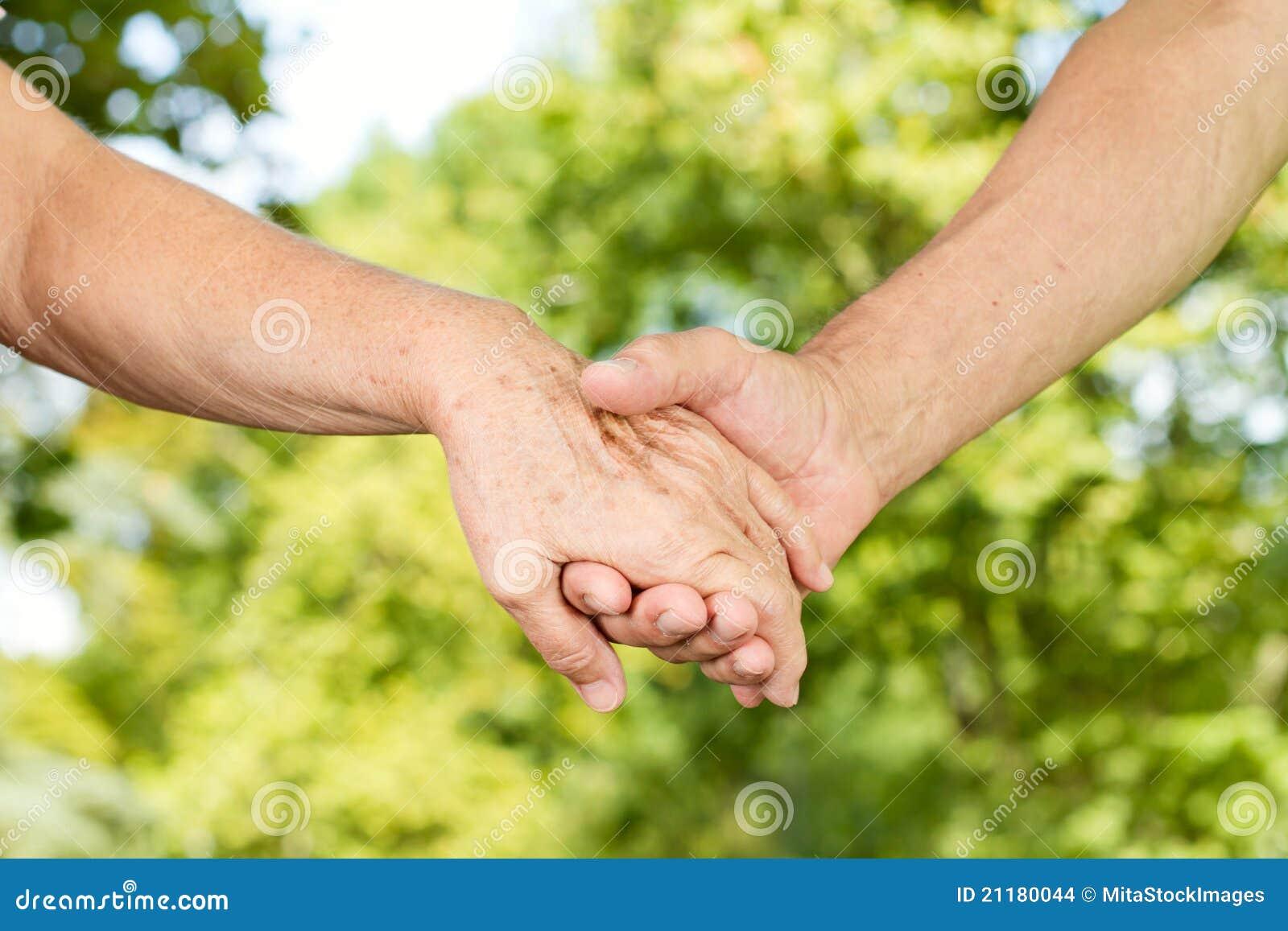 руки держа старые люди совместно