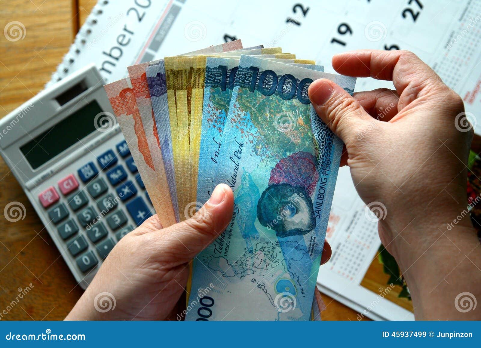 Руки держа счеты денег и калькулятор и календарь